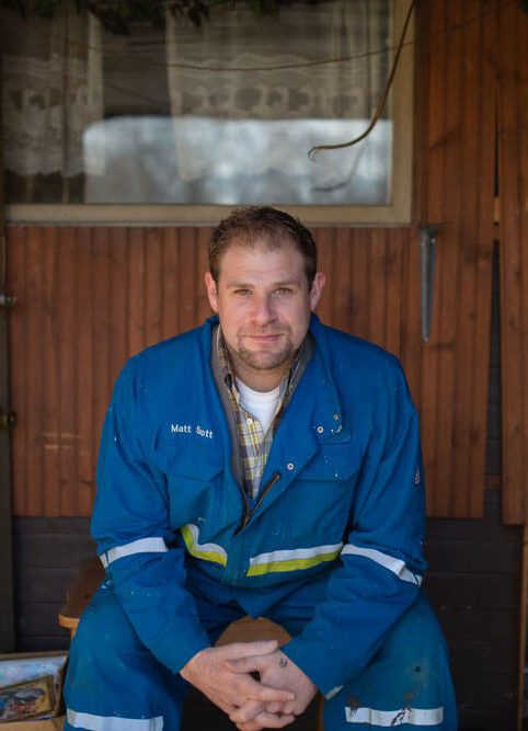 Matt Scott private home buyer is sitting in blue work coveralls on a new home project site