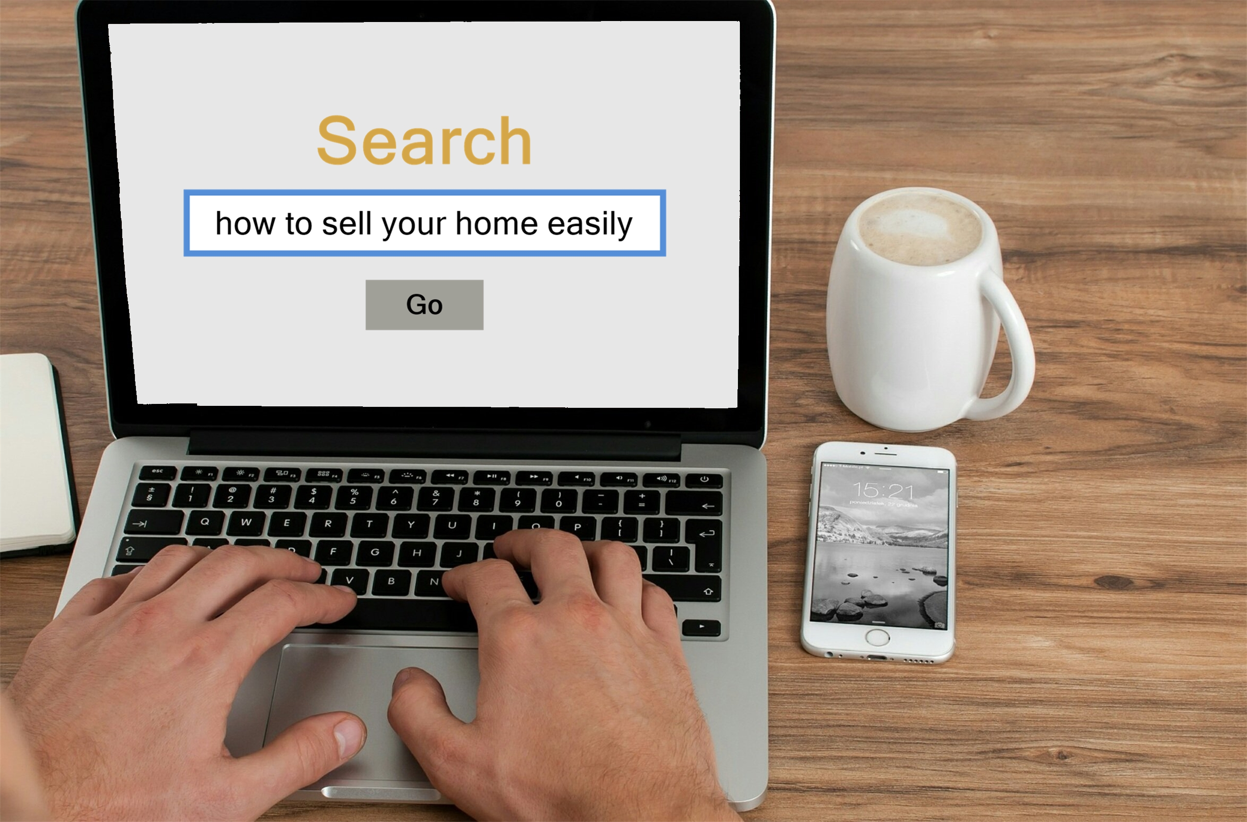 A person using a laptop beside a coffee mug and smartphone searching how to sell your home easily