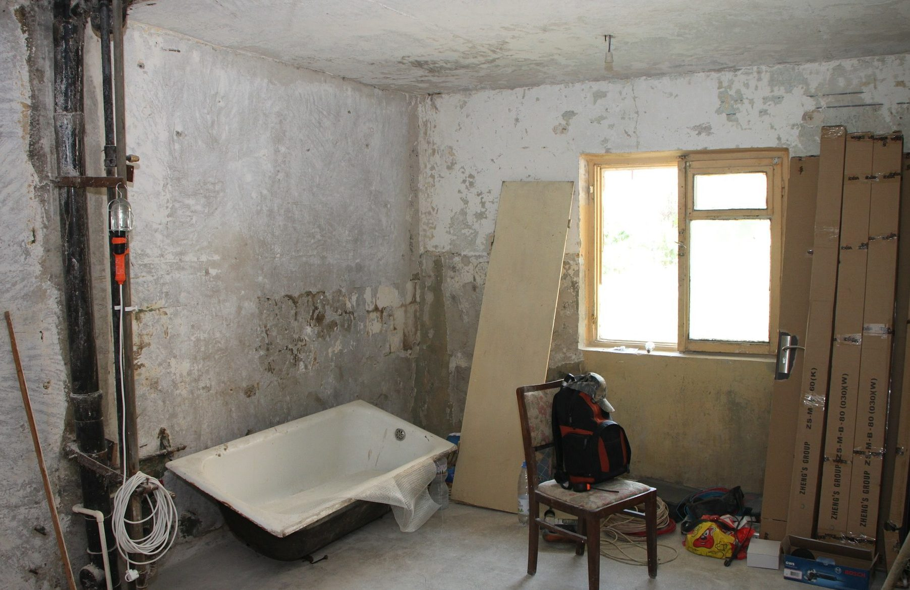 Room in complete disrepair with no wall or floor coverings, broken bathtub, wood and doors leaning against wall, exposed pipe. Tools sitting on a chair and floor awaiting repairs.