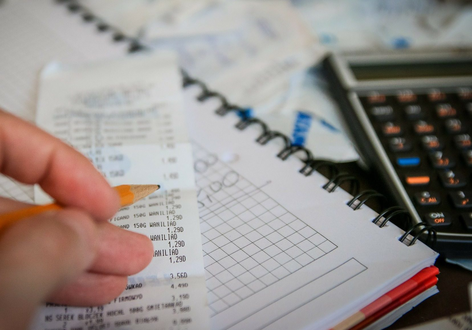 Person holding a pencil over receipt sitting on graph paper and invoices beside a calculator analyzing expenses and profit