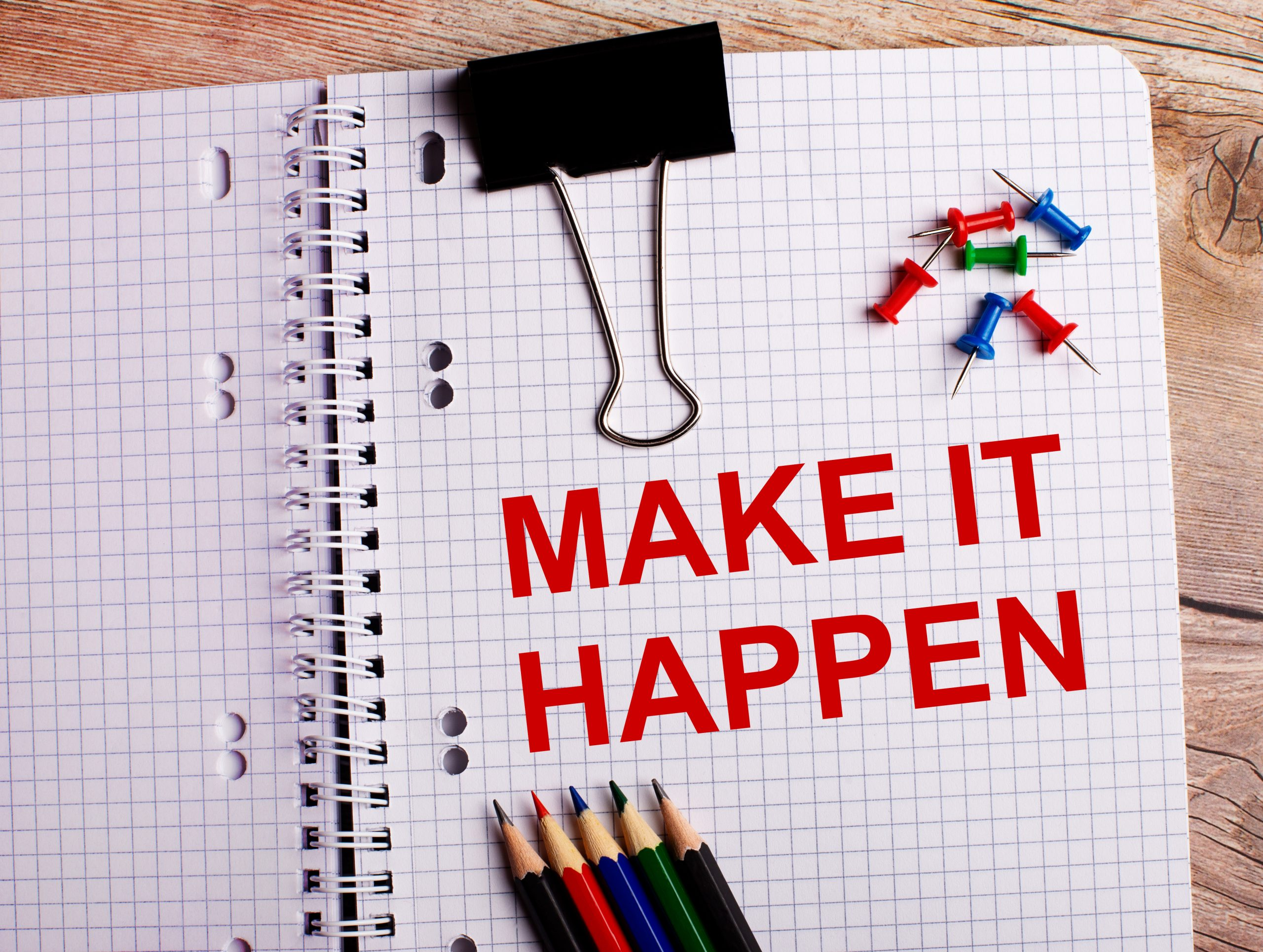 The words MAKE IT HAPPEN is written in a notebook near multi-colored pencils and buttons on a wooden background.