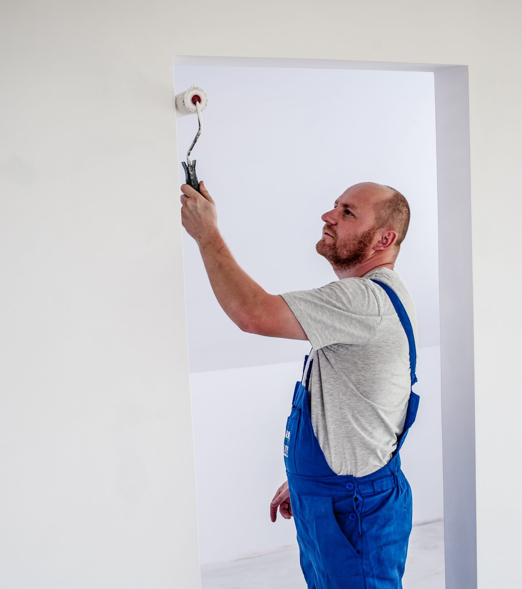 Man in blue overalls painting house white prepare house for sale
