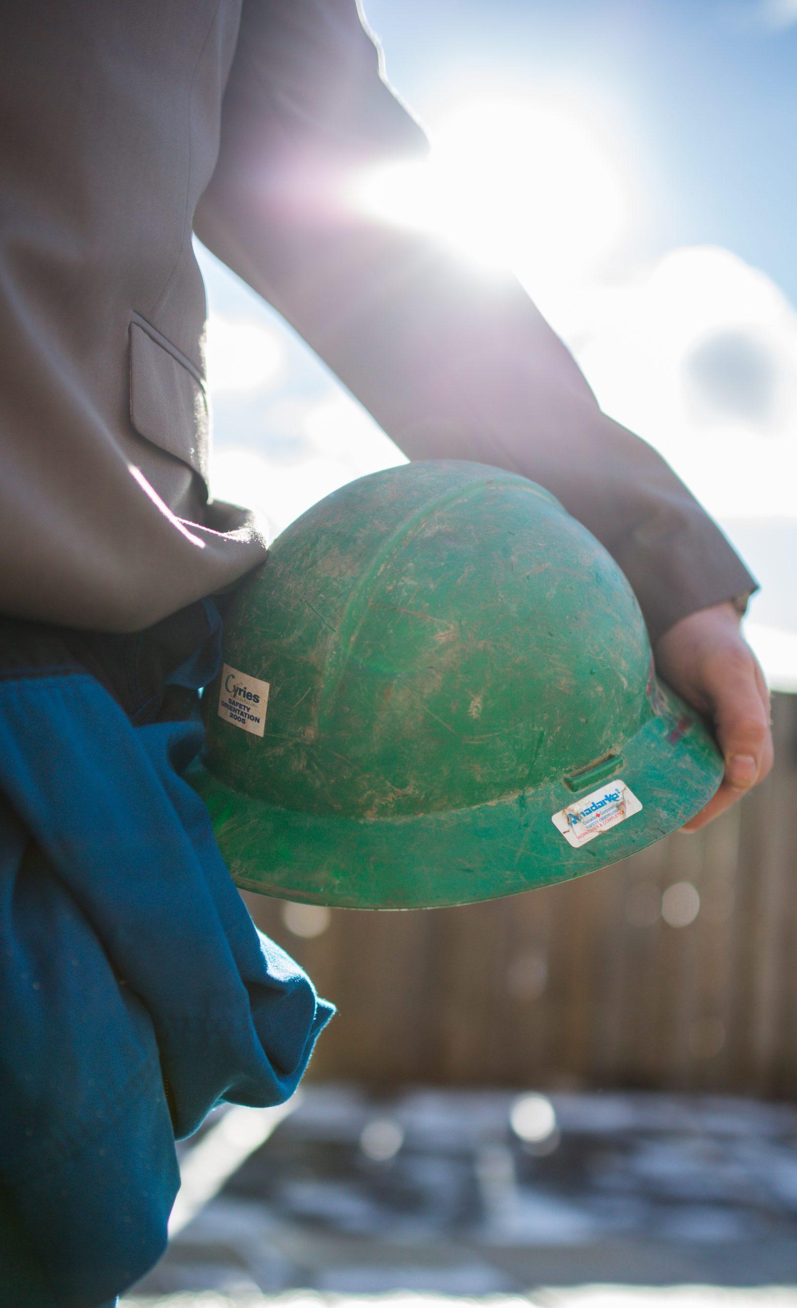 Matt Scott wearing blue coveralls holding green construction hard hat on his hip