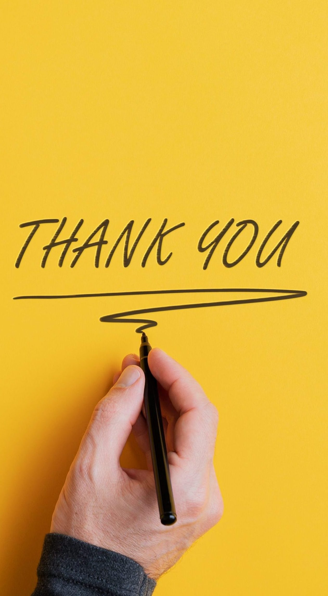 Male hand writing a Thank you sign with black marker on a yellow background sharing gratitude in difficult times